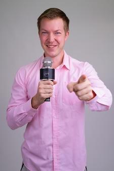 Junger hübscher geschäftsmann mit rosa hemd