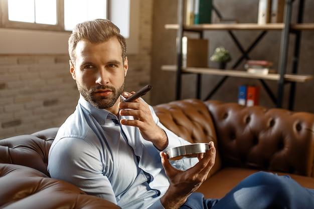 Junger hübscher geschäftsmann raucht zigarre in seinem eigenen büro. er hält es und aschetopf. guy schaut zur seite. vertrauen. tageslicht.