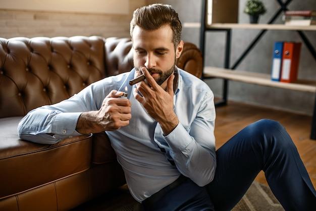 Junger hübscher geschäftsmann raucht zigarre in seinem eigenen büro. er sitzt auf dem boden und lehnt sich zum sofa. guy hält zigarettenanzünder. sexy und konzentriert.