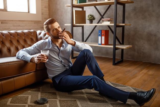 Junger hübscher geschäftsmann raucht zigarre und hält glas whisky in seinem eigenen büro. er sitzt auf dem boden und sieht selbstbewusst aus. sexy junger mann entspannt.