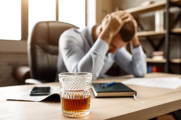 Junger hübscher geschäftsmann sitzt am tisch und leidet unter kater in seinem eigenen büro. er hält die hände auf dem kopf. vorne steht ein glas whisky.