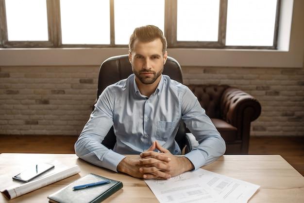 Junger hübscher geschäftsmann sitzt am tisch und posiert in seinem eigenen büro. er schaut direkt vor die kamera. notizbuch und telefon auf dem schreibtisch.