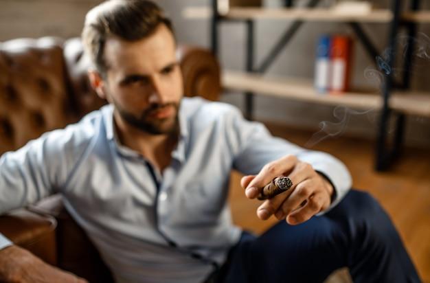 Junger hübscher geschäftsmann sitzt auf boden und hol zigarre in seinem eigenen büro. er sieht mit zuversicht direkt aus. cool und sexy.