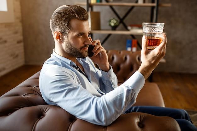 Junger hübscher geschäftsmann sitzt auf sofa und betrachtet glas des whiskys in der hand in seinem eigenen büro. guy telefoniert. ernst und konzentriert. sexy junger mann.