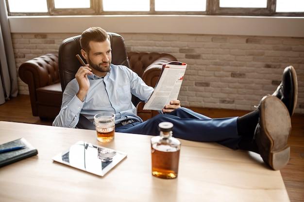 Junger hübscher geschäftsmann sitzt auf stuhl und liest tagebuch in seinem eigenen büro. er hält die zigarre in der hand und die beine auf dem tisch. tablette mit glas whisky und graphen stehen zusammen.