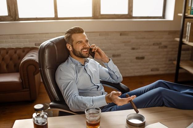 Junger hübscher geschäftsmann sitzt auf stuhl und telefoniert in seinem eigenen büro. er hält die beine auf dem tisch und lächelt. zigarre in der hand. selbstbewusst und positiv.