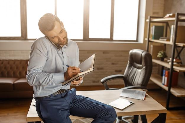 Junger hübscher geschäftsmann sitzt auf tisch und telefoniert in seinem eigenen büro. er schreibt in ein notizbuch. geschäftsanruf. tageslicht aus dem fenster.