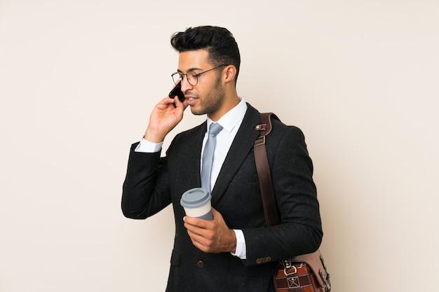 Junger hübscher geschäftsmannmann, der kaffee hält, um lokalisierte wand wegzunehmen
