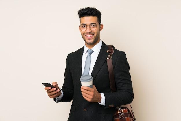 Junger hübscher geschäftsmannmann, der kaffee hält, um lokalisierten hintergrund wegzunehmen