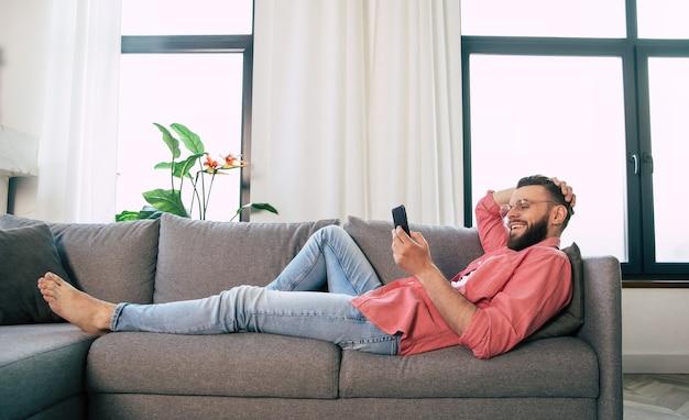 Junger hübscher glücklicher bärtiger mann in der brille benutzt smartphone zum surfen im netz, tippen und chatten, spielen oder arbeiten mit einigen apps, während er sich auf der couch zu hause entspannt