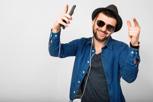 Junger hübscher glücklicher lächelnder mann, der musik in den kopfhörern lokalisiert auf weißem studiohintergrund hört, smartphone hält, jeanshemd, hut und sonnenbrille tragend