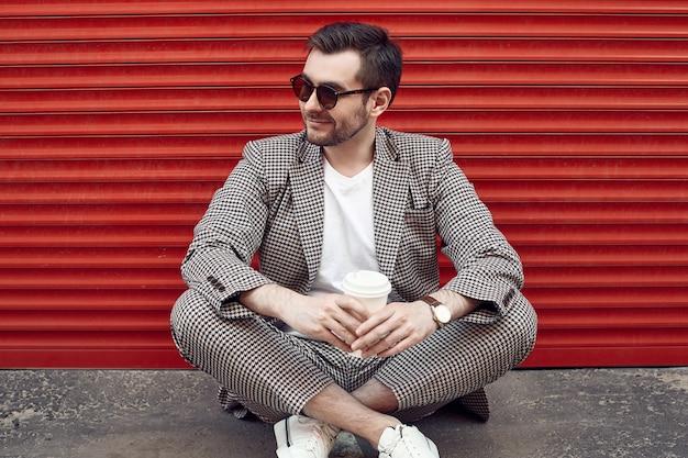 Junger hübscher grober mann in einer modeklage nahe dem roten tor