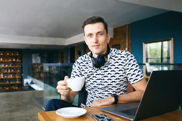 Junger hübscher hippie-mann, der im café, tasse kaffee halten sitzt. laptop und handy auf holztisch.