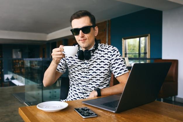 Junger hübscher hippie-mann in der sonnenbrille, die im café, tasse kaffee halten sitzt. laptop und handy auf holztisch.