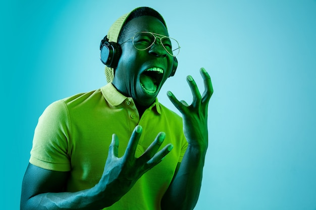 Junger hübscher hipster-mann, der musik mit kopfhörern hört