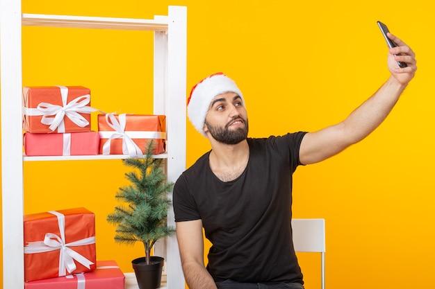Junger hübscher hipster-mann in einem weihnachtsmannhut, der ein selfie auf einem smartphone an der wand der grußgeschenke und eines neujahrsbaums auf einem gelben hintergrund macht. neujahrs- und weihnachtskonzept.