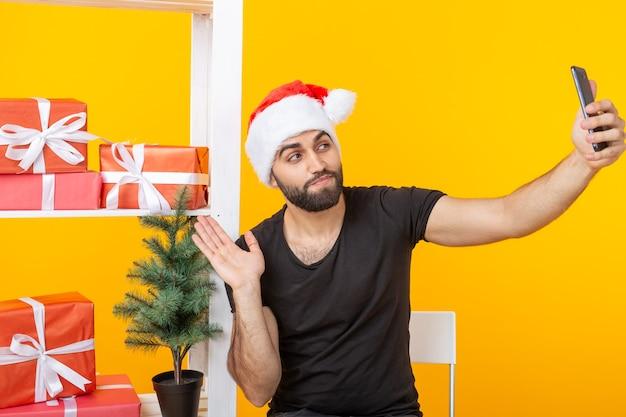 Junger hübscher hipster-mann in einem weihnachtsmannhut, der ein selfie auf einem smartphone auf der oberfläche von macht