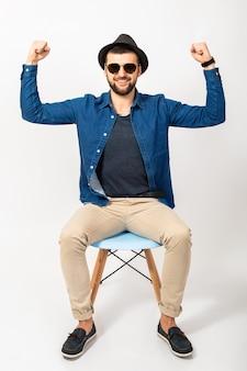 Junger hübscher hipster-mann, isolierter weißer studiohintergrund, stilvolles outfit, jeanshemd, hose, hut, sonnenbrille, auf stuhl sitzend, erfolg, gewinn, emotional, glücklich, lächelnd