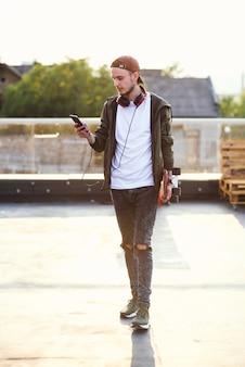 Junger hübscher hipster-mann mit skateboard unter verwendung des telefons auf dem dachspielplatz des industriegebäudes.