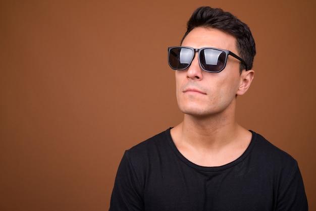 Junger hübscher hispanischer mann auf brauner wand