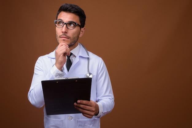Junger hübscher hispanischer mannarzt gegen braunen hintergrund