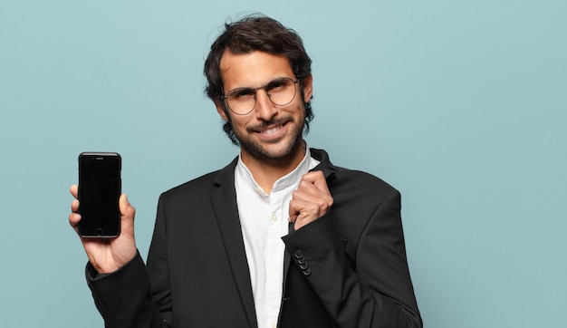 Junger hübscher indischer businesman, der sein telefon leeren bildschirm zeigt
