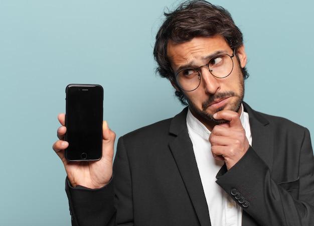 Junger hübscher indischer businesman, der seinen leeren bildschirm des telefons zeigt