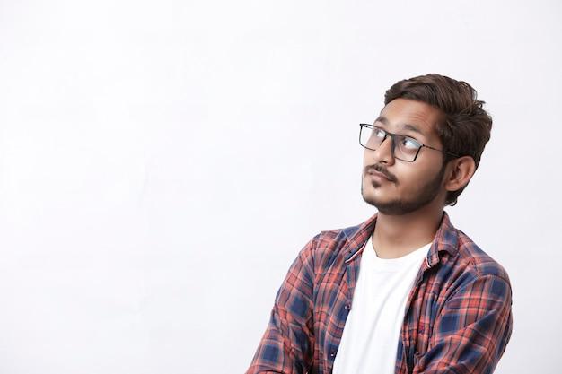 Junger hübscher indischer college-student, der denkenden ausdruck auf weißem hintergrund gibt