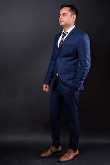Junger hübscher indischer geschäftsmann, der blauen anzug gegen schwarze wand trägt