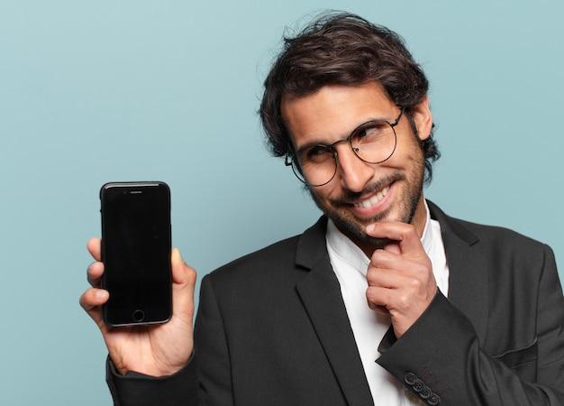 Junger hübscher indischer geschäftsmann, der seinen leeren bildschirm des telefons zeigt