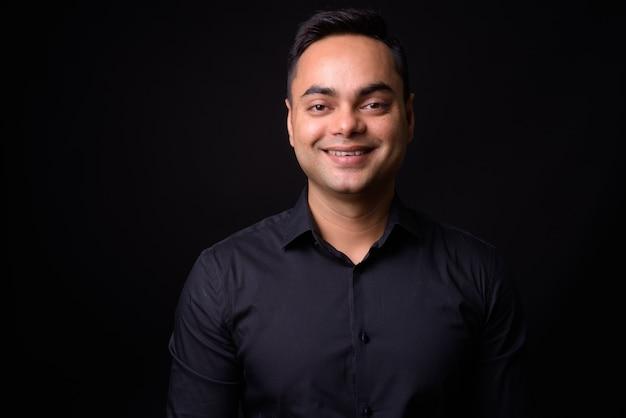 Junger hübscher indischer geschäftsmann gegen schwarze wand