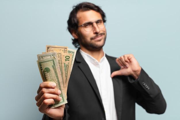 Junger hübscher indischer geschäftsmann mit banknoten bank
