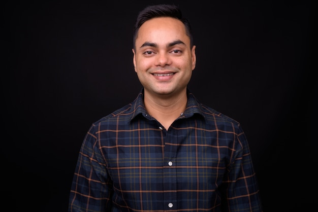 Junger hübscher indischer hipster-mann gegen schwarze wand