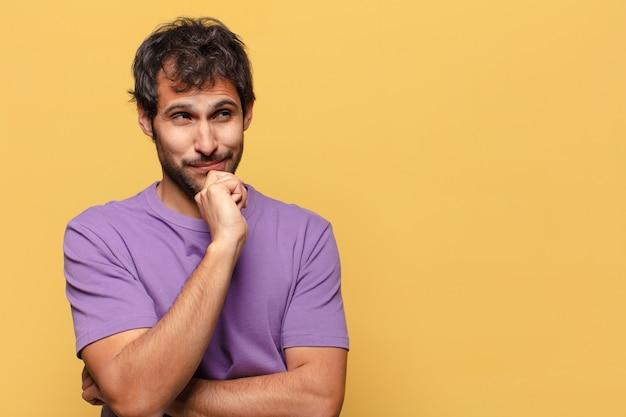 Junger hübscher indischer mann. denkender oder zweifelnder ausdruck