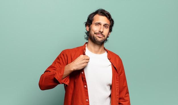 Junger hübscher indischer mann, der arrogant, erfolgreich, positiv und stolz aussieht und auf sich selbst zeigt