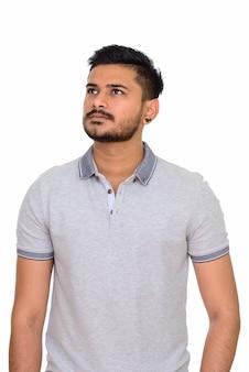 Junger hübscher indischer mann, der denkt und aufschaut