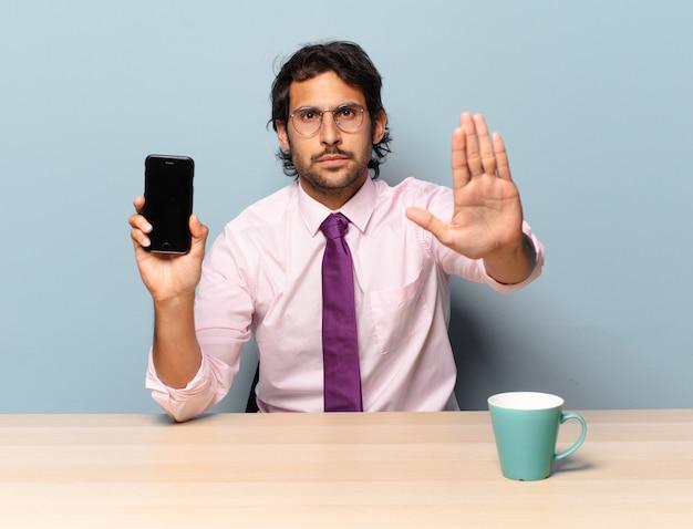 Junger hübscher indischer mann, der ernst, streng, unzufrieden und wütend aussieht und offene handfläche zeigt, die stoppgeste macht.