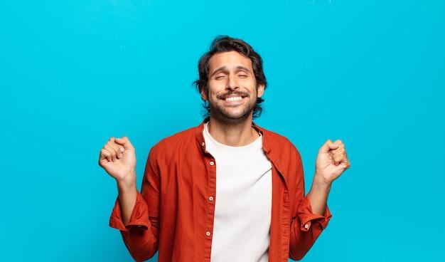 Junger hübscher indischer mann, der extrem glücklich und überrascht aussieht, erfolg feiert, schreit und springt