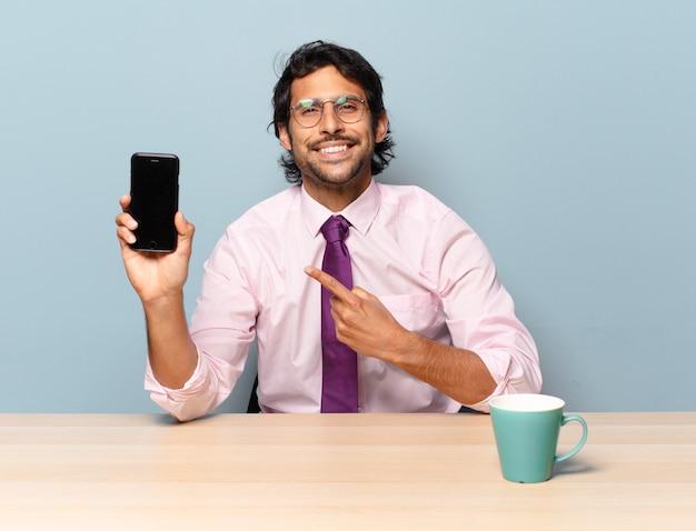 Junger hübscher indischer mann, der fröhlich lächelt, sich glücklich fühlt und zur seite und nach oben zeigt und objekt im kopienraum zeigt. unternehmenskonzept
