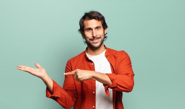 Junger hübscher indischer mann, der fröhlich lächelt und zeigt, um raum auf handfläche auf der seite zu kopieren, ein objekt zeigend oder werbend