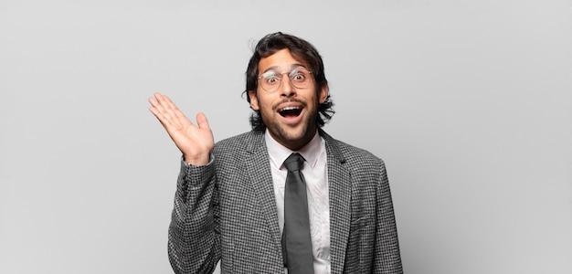 Junger hübscher indischer mann, der glücklich, überrascht und fröhlich fühlt, mit positiver einstellung lächelt und eine lösung oder idee verwirklicht. geschäftskonzept