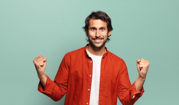 Junger hübscher indischer mann, der glücklich, überrascht und stolz fühlt, schreit und erfolg mit einem großen lächeln feiert
