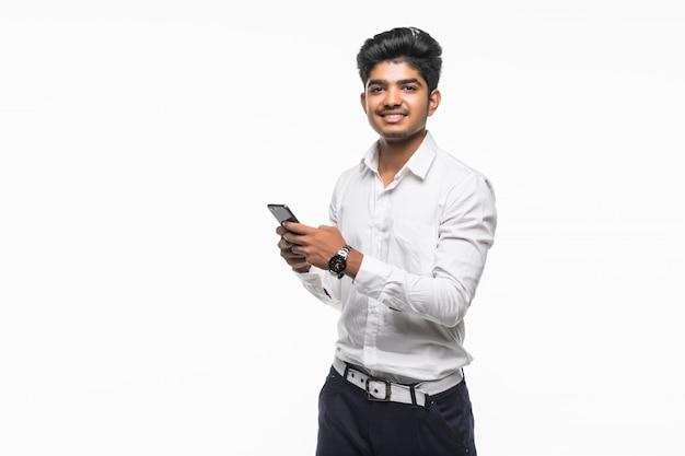 Junger hübscher indischer mann, der handy isoated auf weißer wand verwendet