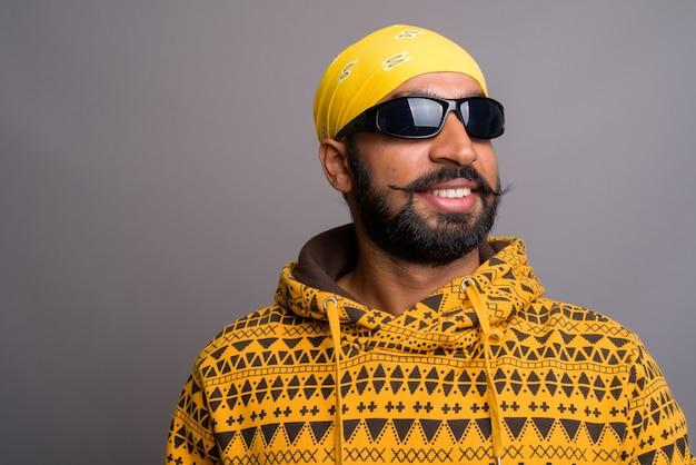 Junger hübscher indischer mann, der kapuzenpulli beim denken trägt
