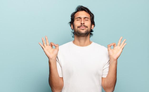 Junger hübscher indischer mann, der konzentriert und meditierend aussieht, sich zufrieden und entspannt fühlt, denkt oder eine wahl trifft