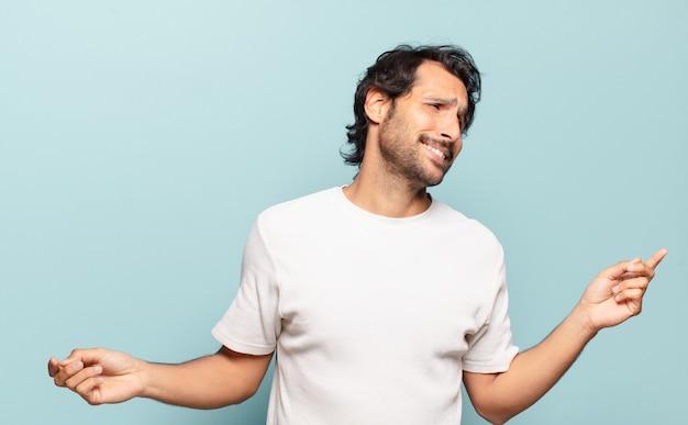 Junger hübscher indischer mann, der lächelt, sich sorglos, entspannt und glücklich fühlt, tanzt und musik hört und spaß auf einer party hat