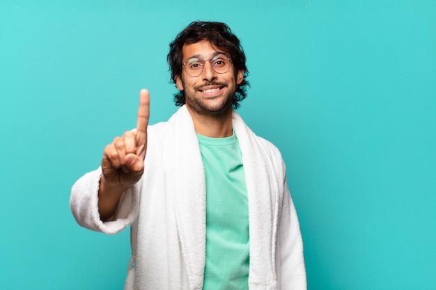 Junger hübscher indischer mann, der lächelt und freundlich schaut, nummer eins oder zuerst mit der hand nach vorne zeigend, herunterzählend und bademantel tragend