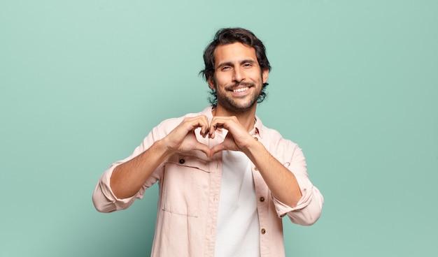 Junger hübscher indischer mann, der lächelt und sich glücklich, süß, romantisch und verliebt fühlt und herzform mit beiden händen bildet