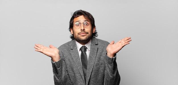 Junger hübscher indischer mann, der sich verwirrt und verwirrt fühlt, zweifelt, gewichtet oder verschiedene optionen mit lustigem ausdruck wählt