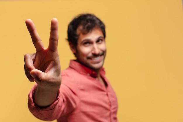 Junger hübscher indischer mann. einen triumph feiern wie ein sieger